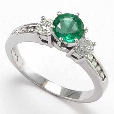 Round shaped diamond and emerald ring